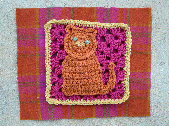 Crochet granny square with a crochet cat appliqued to the top