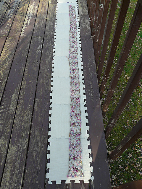 A damp crochet scarf pinned to a blocking board to dry