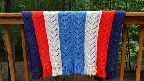 A red, white, and two blues knitted blanket