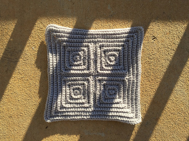 the last crochet square of a gray crochet afghan