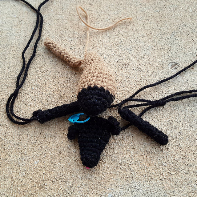 A crochet goat in need of a fourth leg