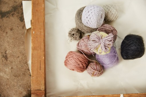a still of left overs of yarn in different colours in a wooden frame