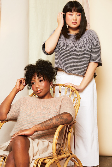 black woman in rattan chair modelling pink sweater and another lady behind the chair modelling the same sweater in a grey colour