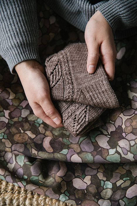 close up of model showing a small stack of folded brown socks