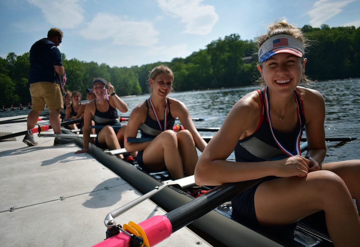 Junior Aidan Wrenn-Walz sits at the finish line dock with the first varsity boat, holding her second place medal at the States championship. The States championship is what rowers at the school spend most of the season preparing for.