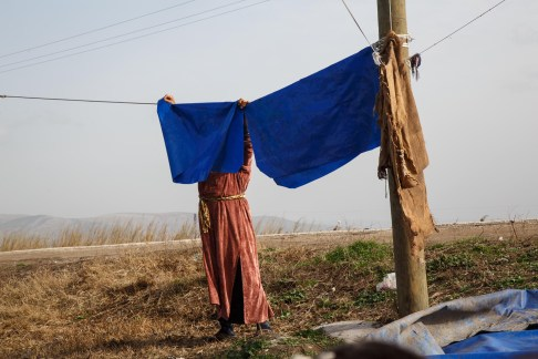 Syrian refugee in South Turkey hangs pieces of tarpaulin to dry after heavy rains. 85% of Syrians in Turkey live outside of the official refugee camps.
