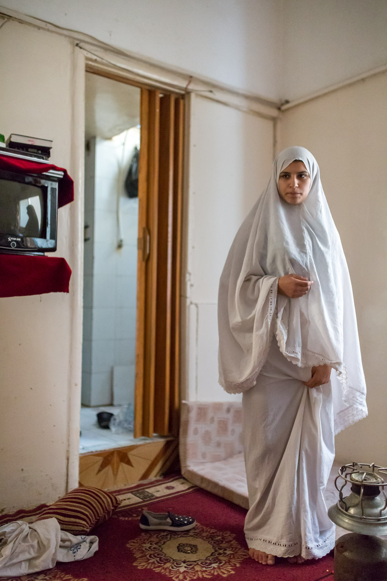 Ada who comes from Damascus, feels sick since two months and can't see a doctor. She has just washed the few clothes she could bring , and wears her prayer gown until the garments are dry.