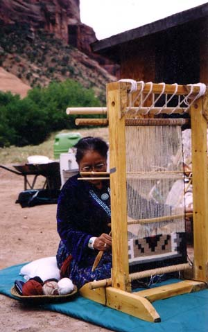 Navajo weaver sitting at loom weaving