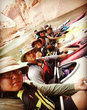 Kayakers lined up on river depicts Adventures for Hopi participants