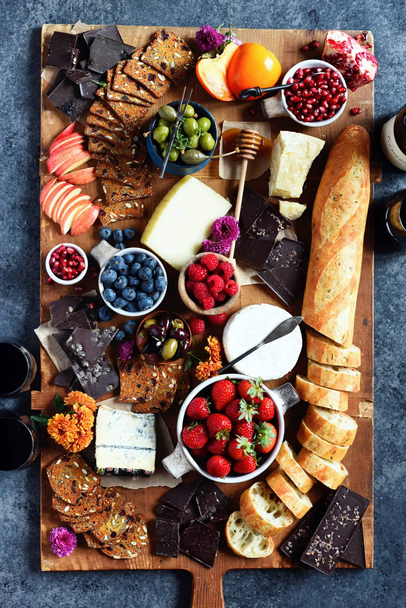 Overhead of cheese board with fresh fruit, bread and crackers