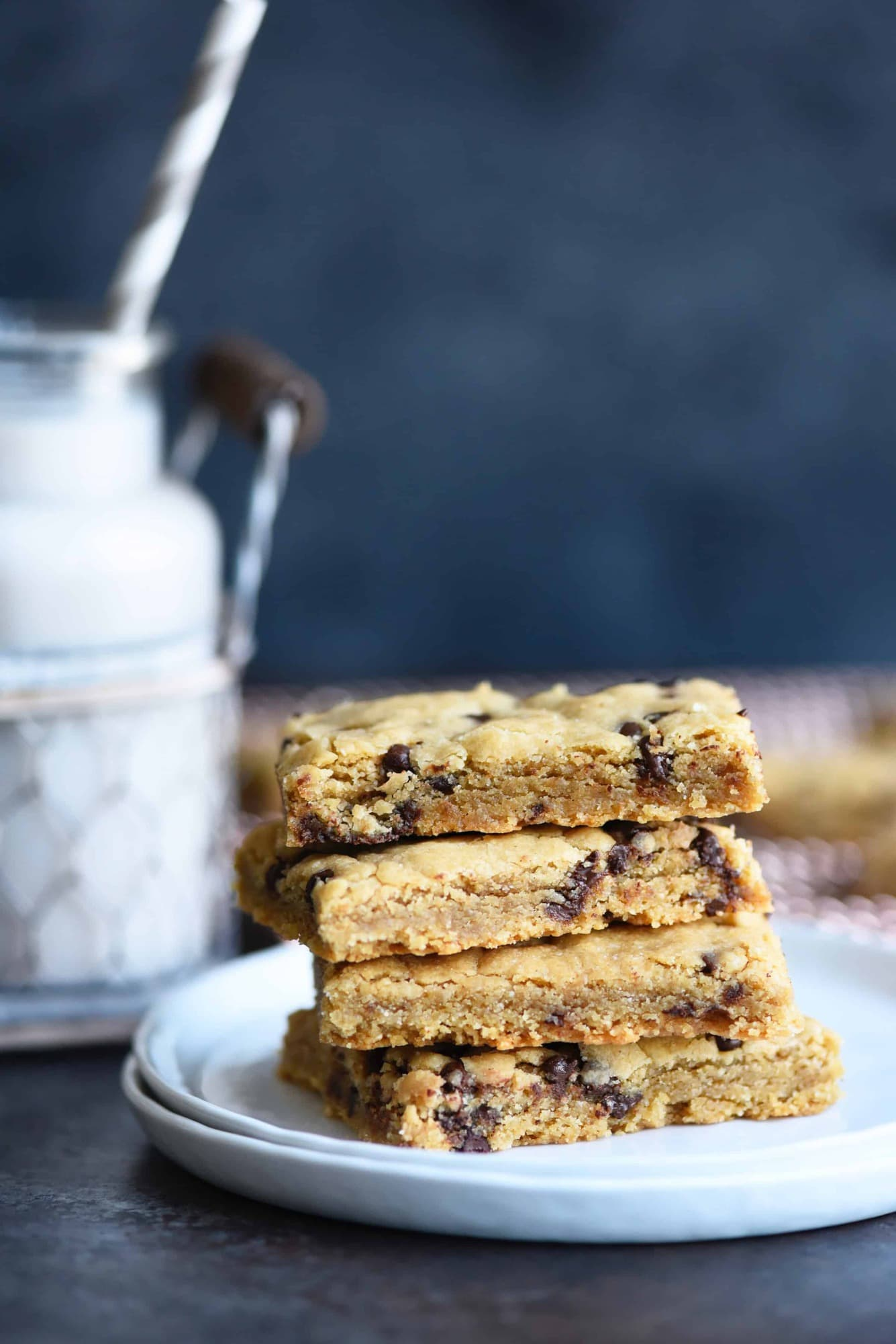 Side view of stack of chocolate chip cookie bars on a white plate with milk in background