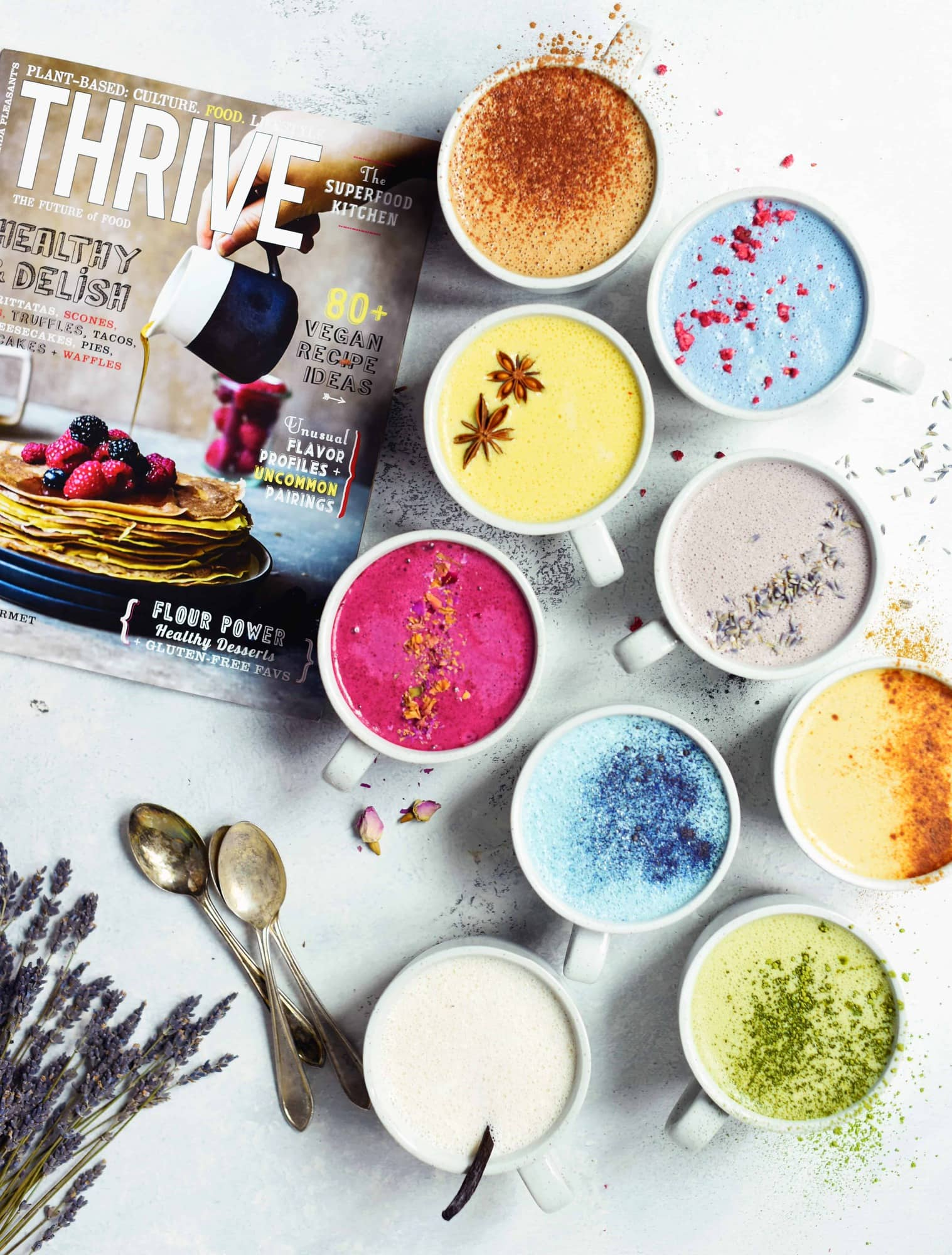 Overhead of naturally colored lattes in white mugs on white background next to Thrive magazine