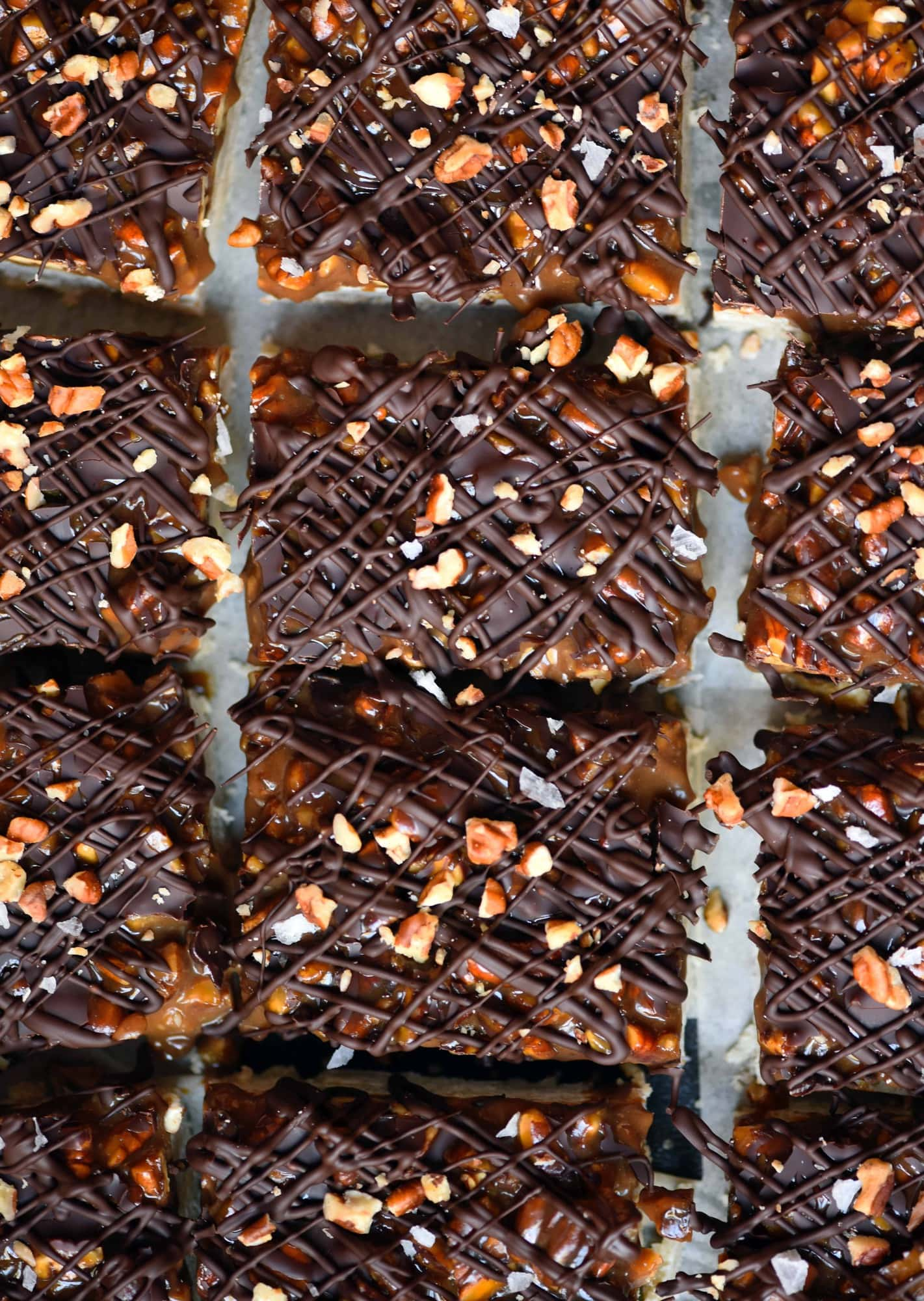 Overhead of pecan caramel shortbread bars with drizzled dark chocolate