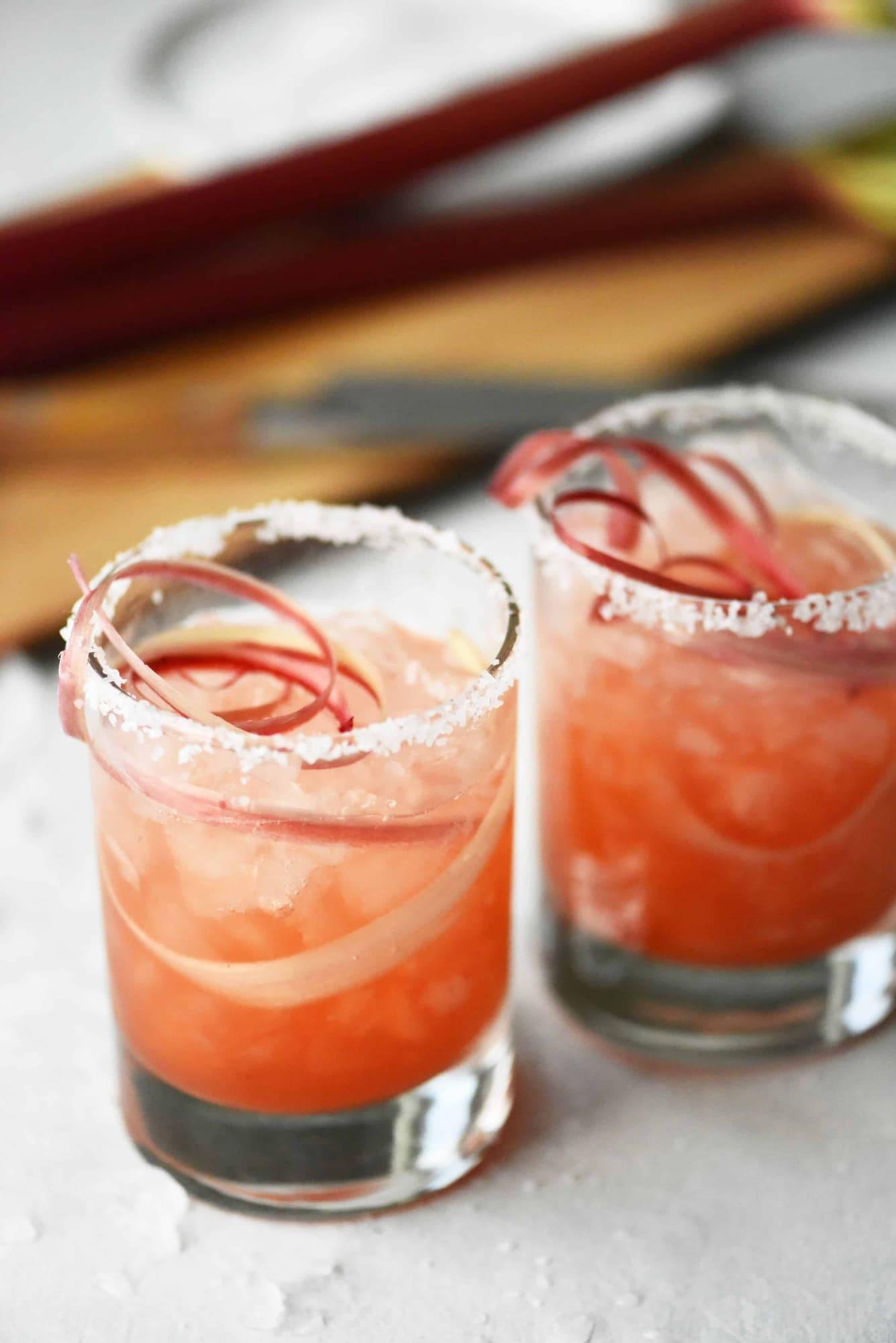 Pouring raspberry rhubarb margarita into glass with rhubarb ribbons