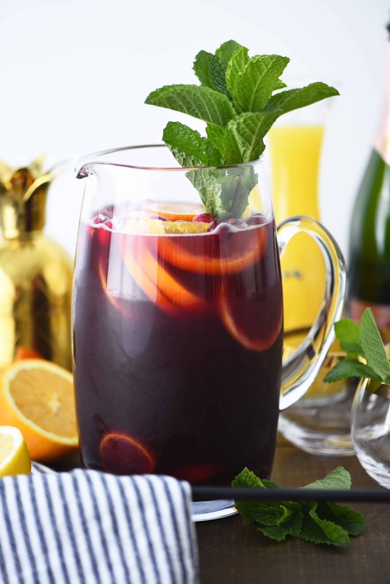 Side view of glass pitcher of holiday punch with citrus and fresh mint