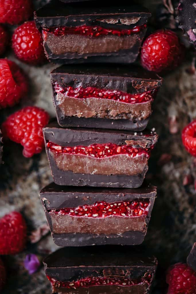 Overhead of chocolate cashew butter cups with raspberry chia jam sliced in half on an antique sheet pan with fresh raspberries