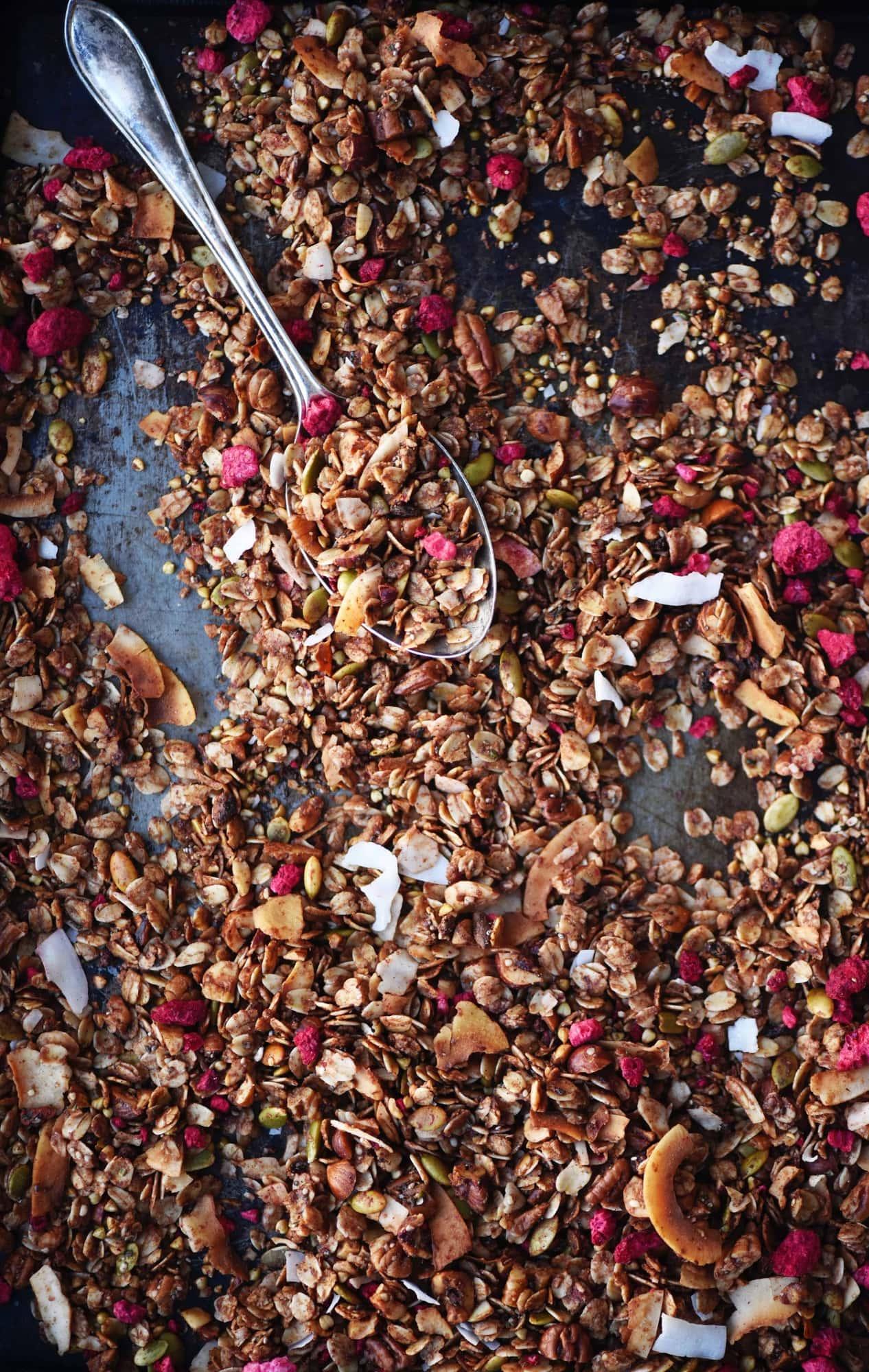 Overhead of chocolate hazelnut raspberry granola on a sheet pan with a large spoon