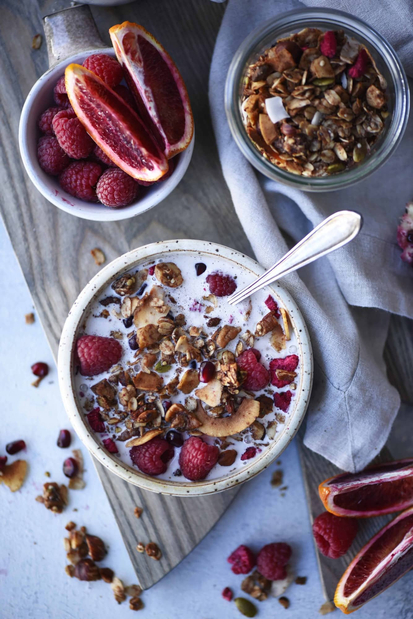 Overhead of bowl of granola with milk and fresh raspberries