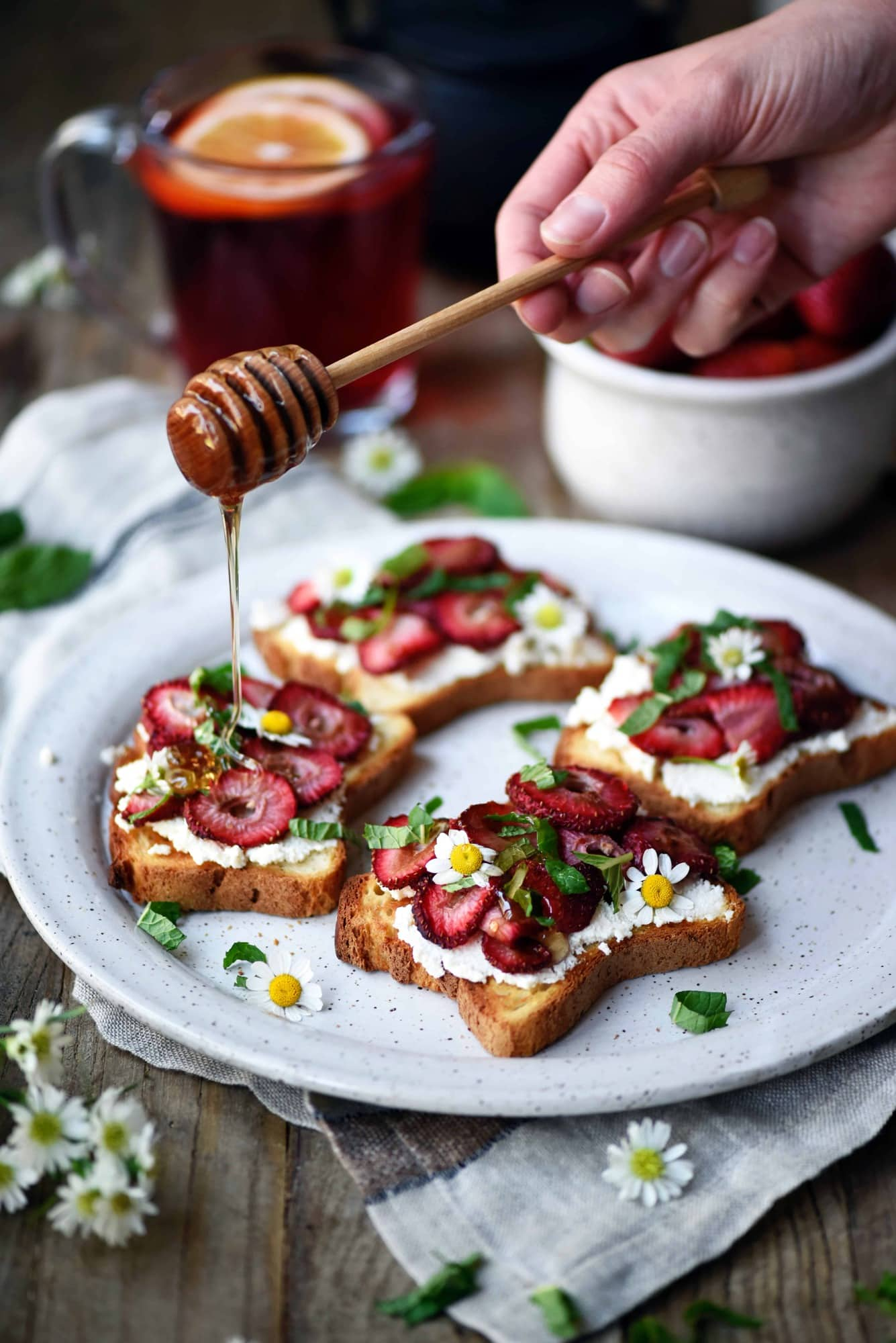 Drizzling honey onto toast topped with ricotta and roasted strawberries