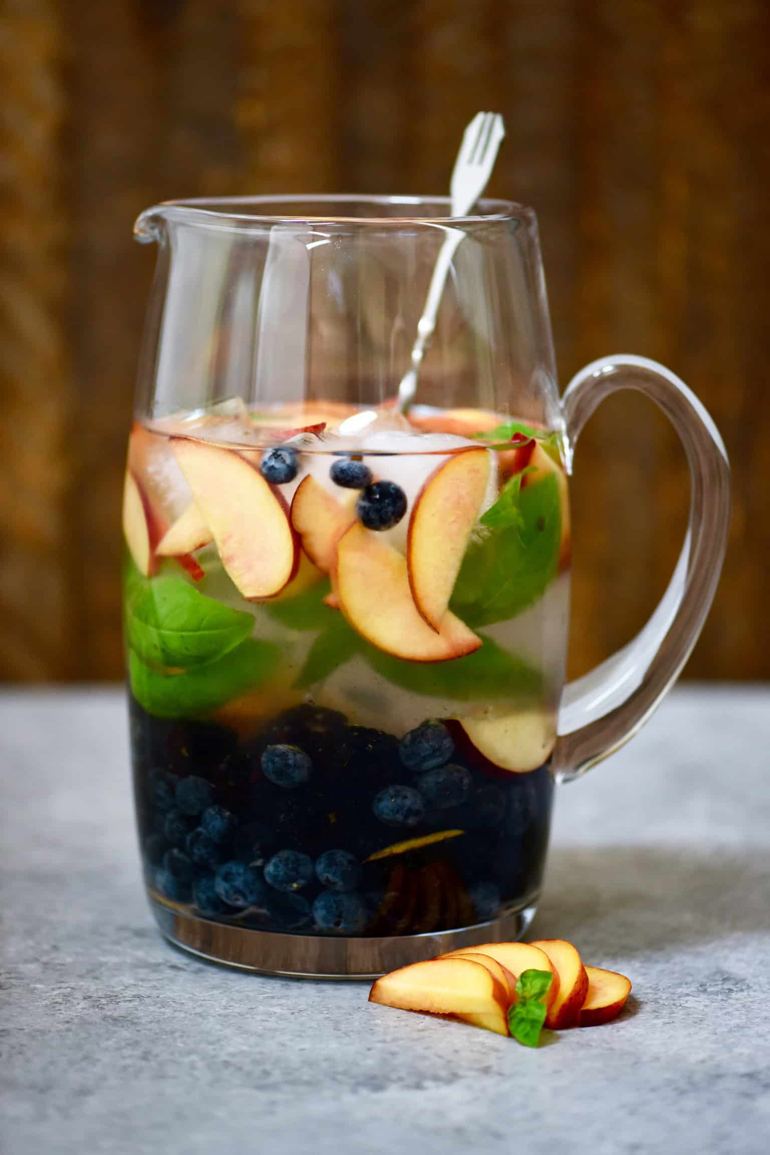 Large pitcher of peach, blueberry and basil infused water