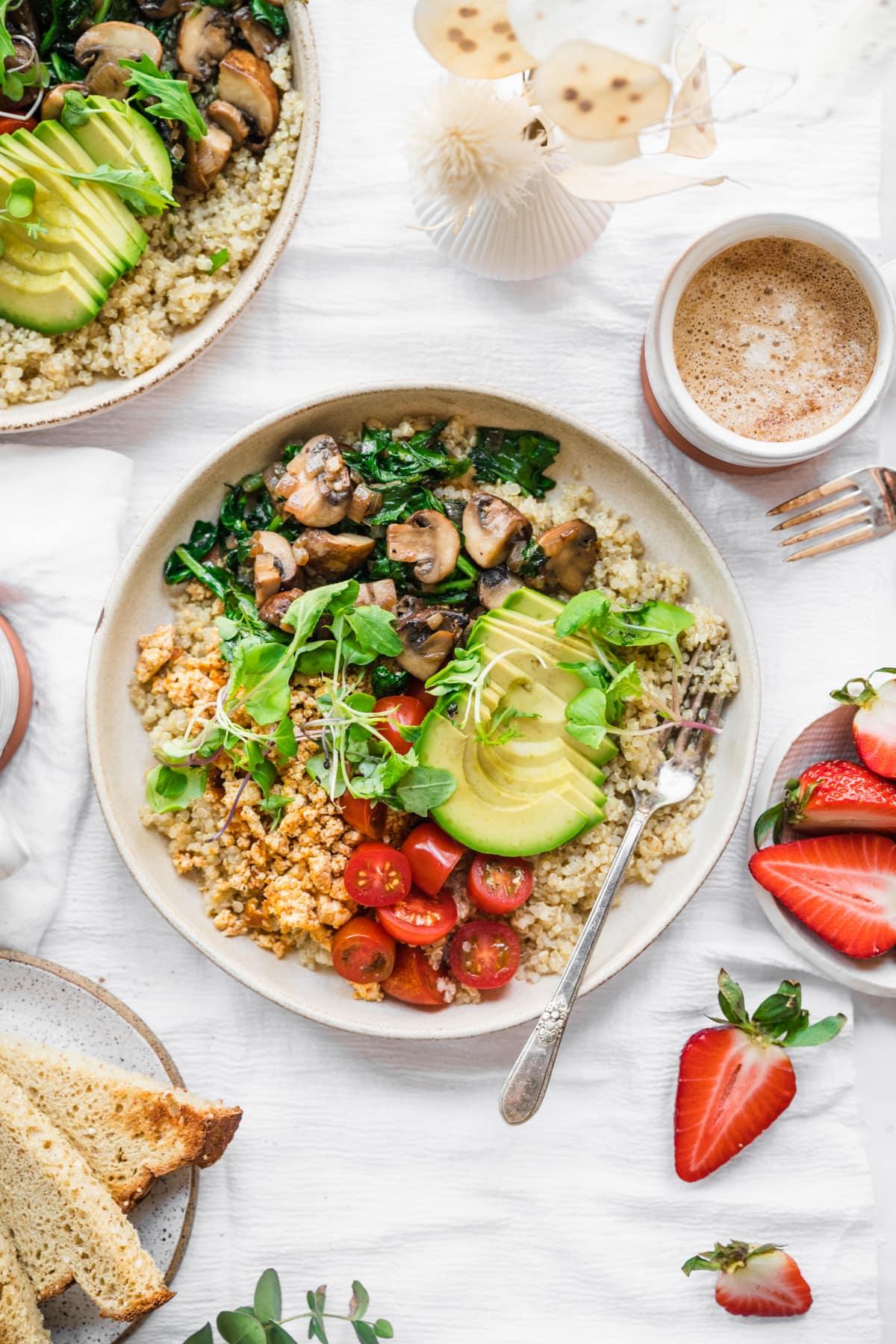 overhead view of vegan savory quinoa breakfast bowl with tofu, avocado and mushrooms.