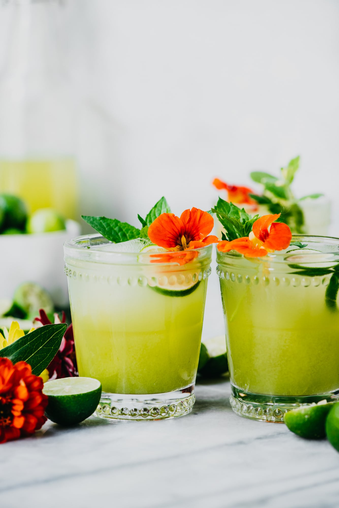 Side view of green cocktail with key limes and flowers
