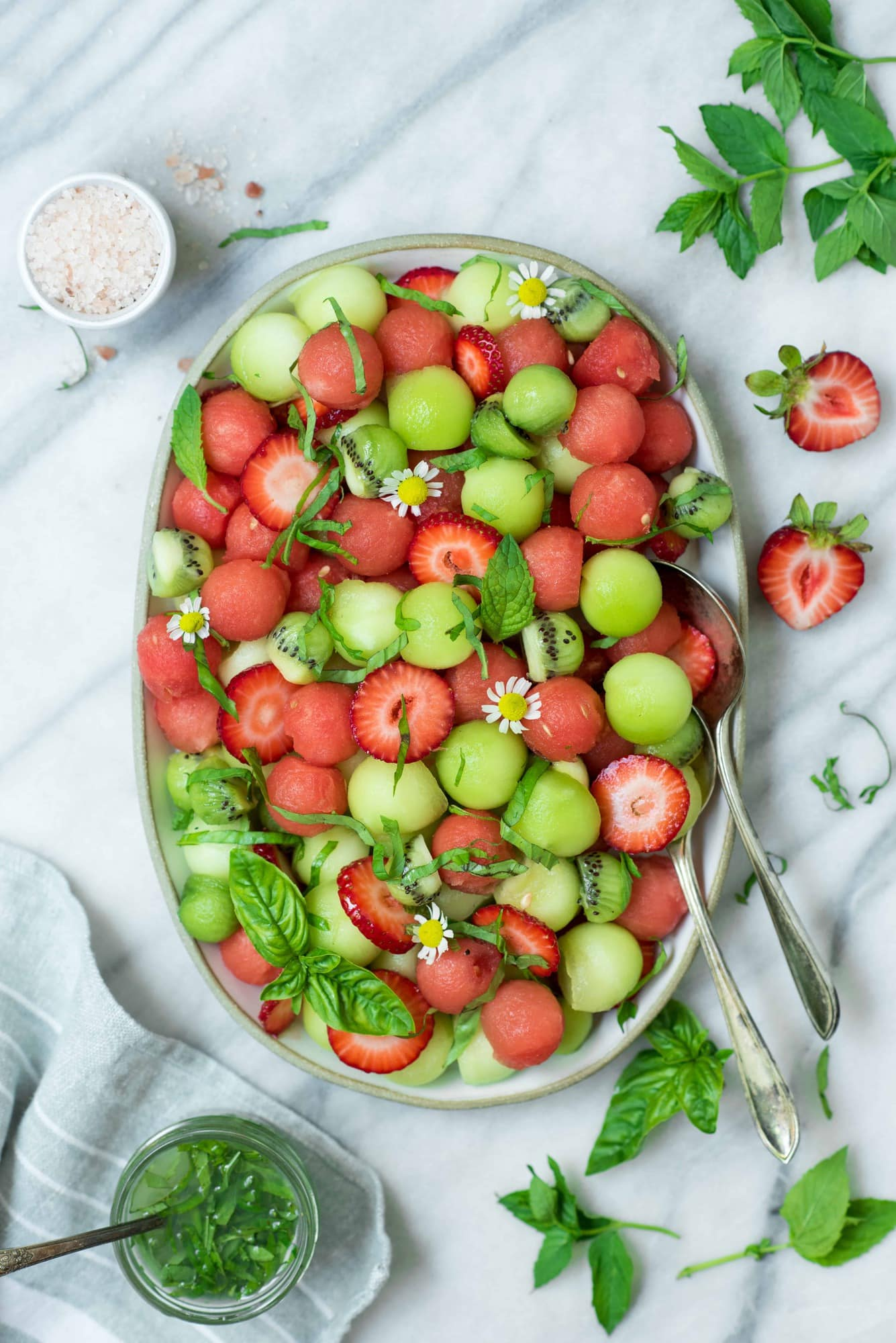 Overhead of melon ball salad on a white platter with strawberries and a lime mint dressing on a white marble backdrop