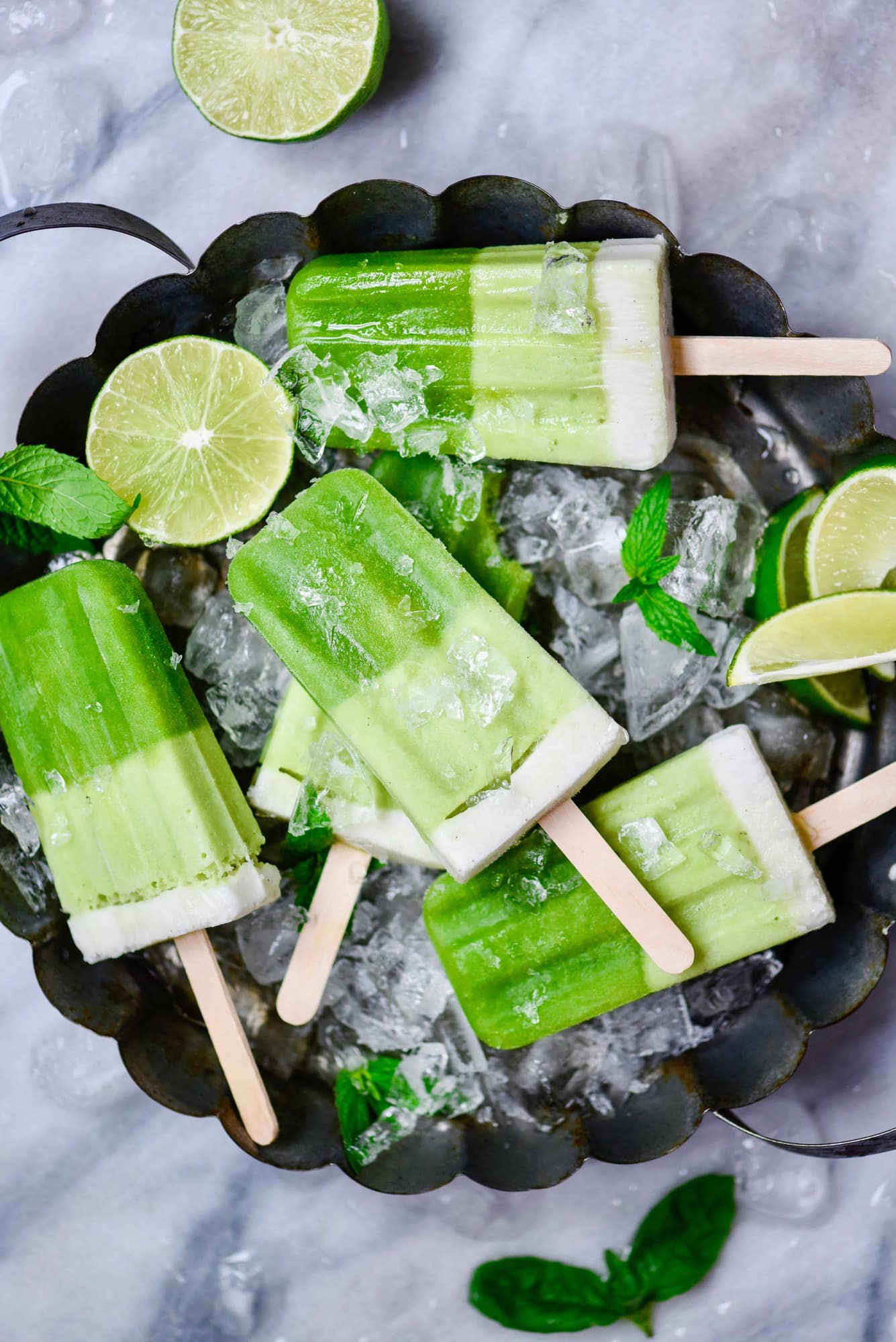 Overhead of green popsicles on a circular tray full of ice