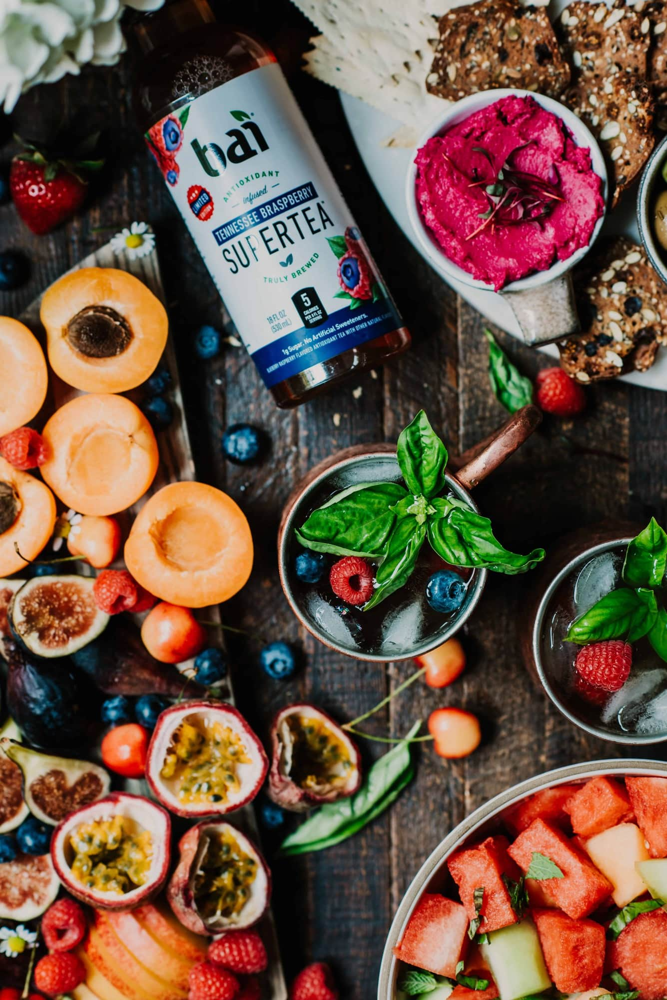 Overhead of fresh summer fruit board and berry moscow mules with fresh basil styled on a rustic wood background
