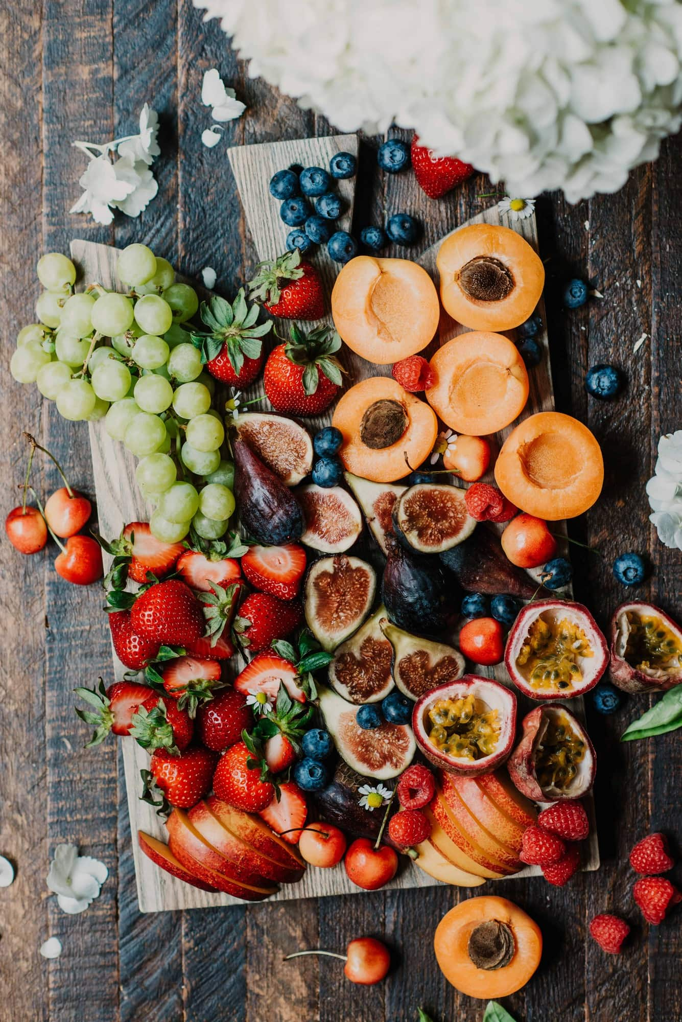 Fresh summer fruit on a wood cutting board and rustic, antique background
