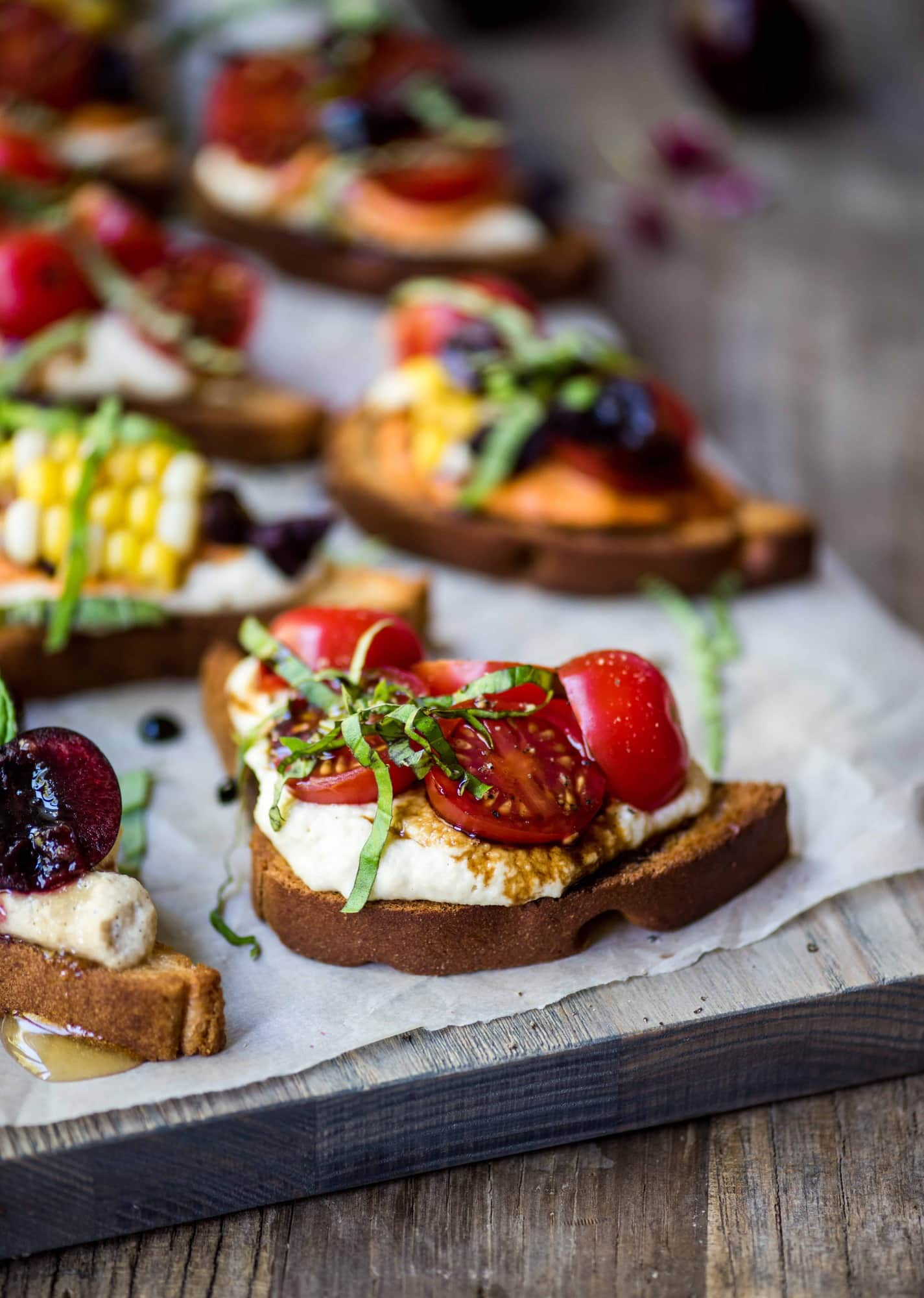 Side view of crostini topped with tomatoes, basil and vegan ricotta