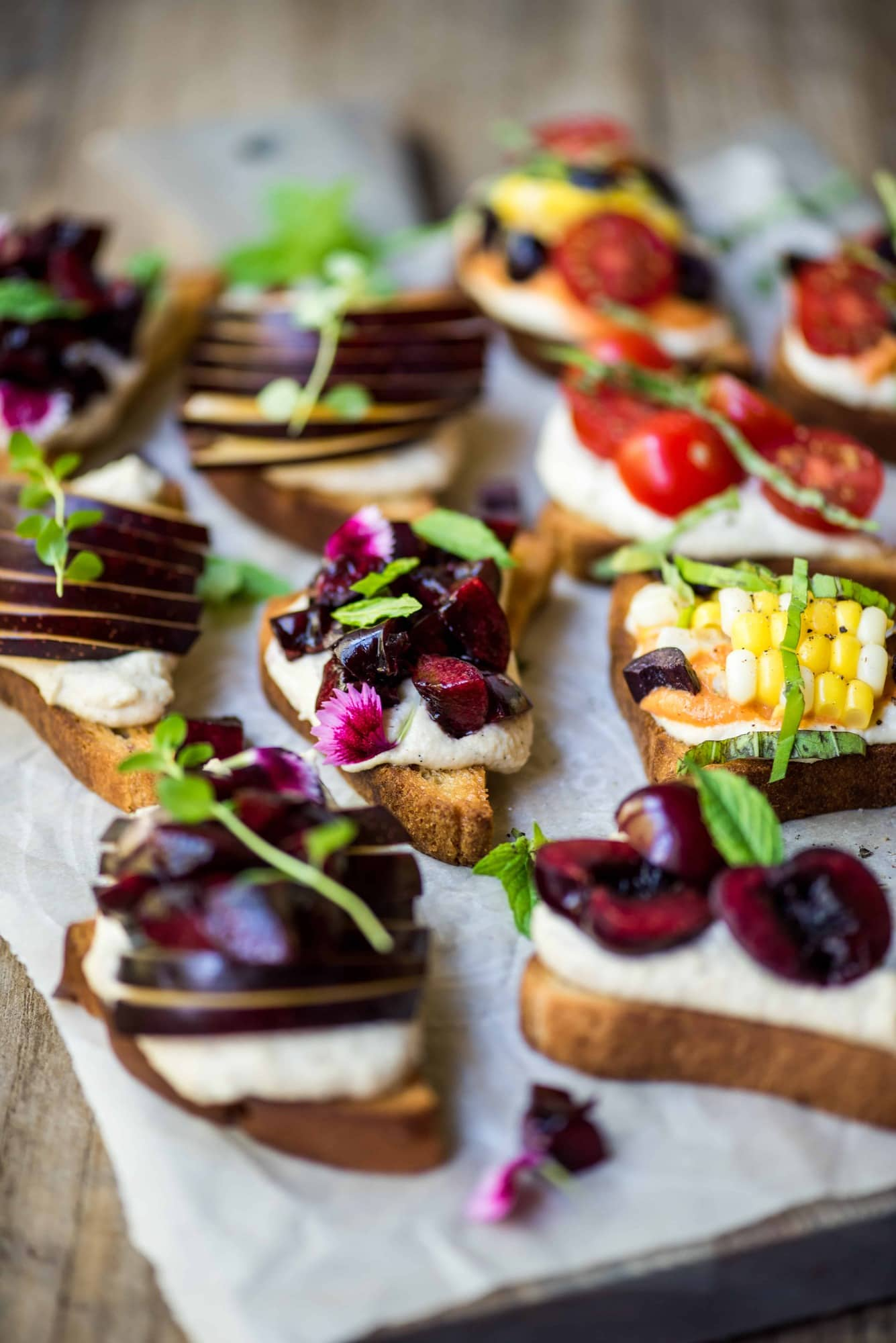 Side angle of crostini topped with cherries, ricotta and herbs