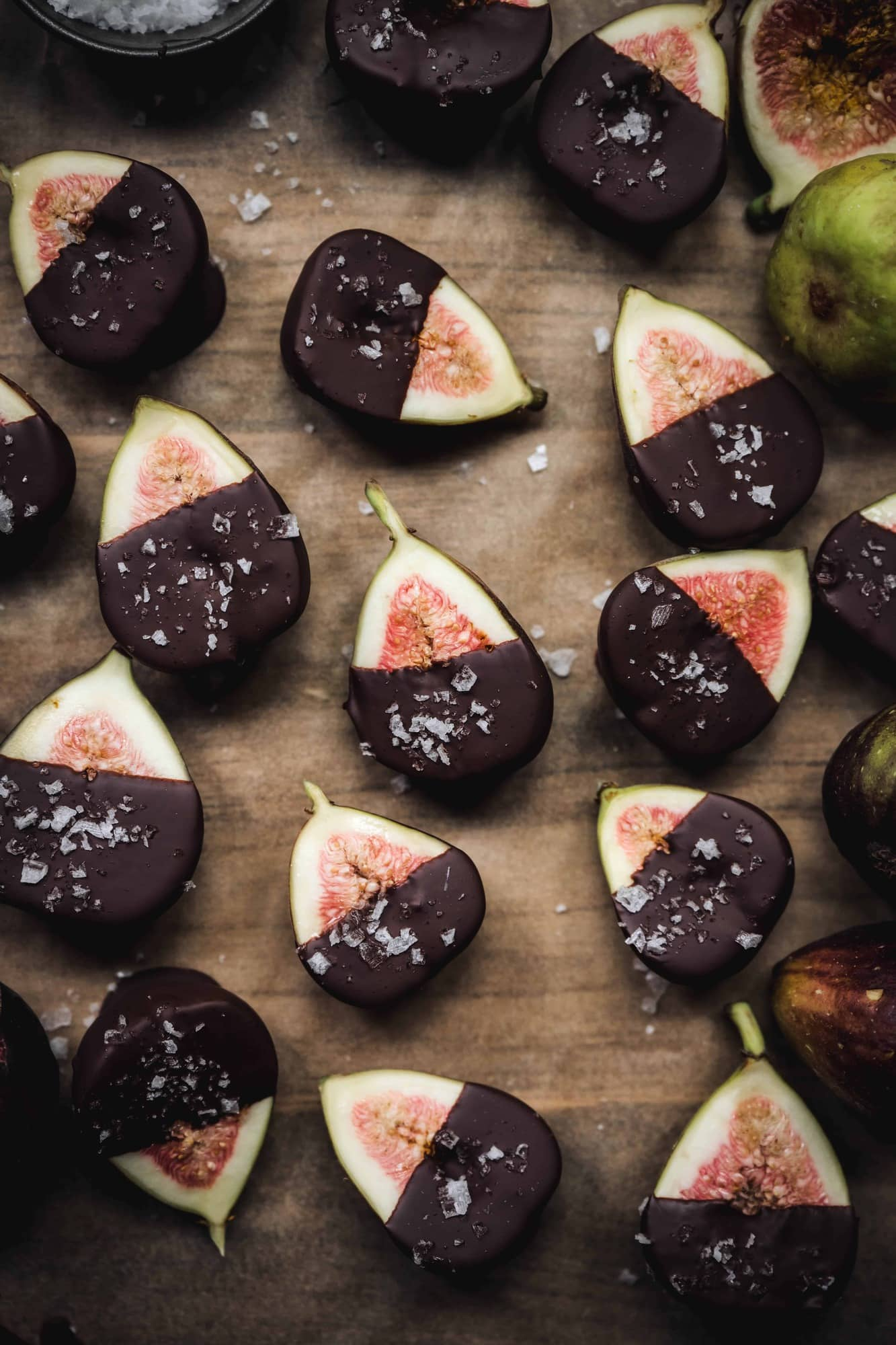 Overhead of dark chocolate dipped figs with sea salt on a white background