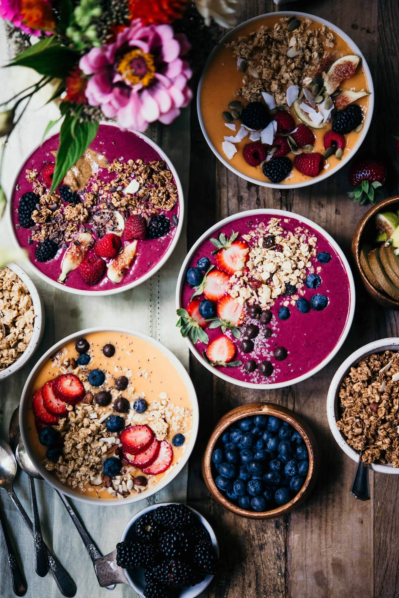 Four pink and orange smoothie bowls topped with fresh berries and granola on a wood table with fresh flowers
