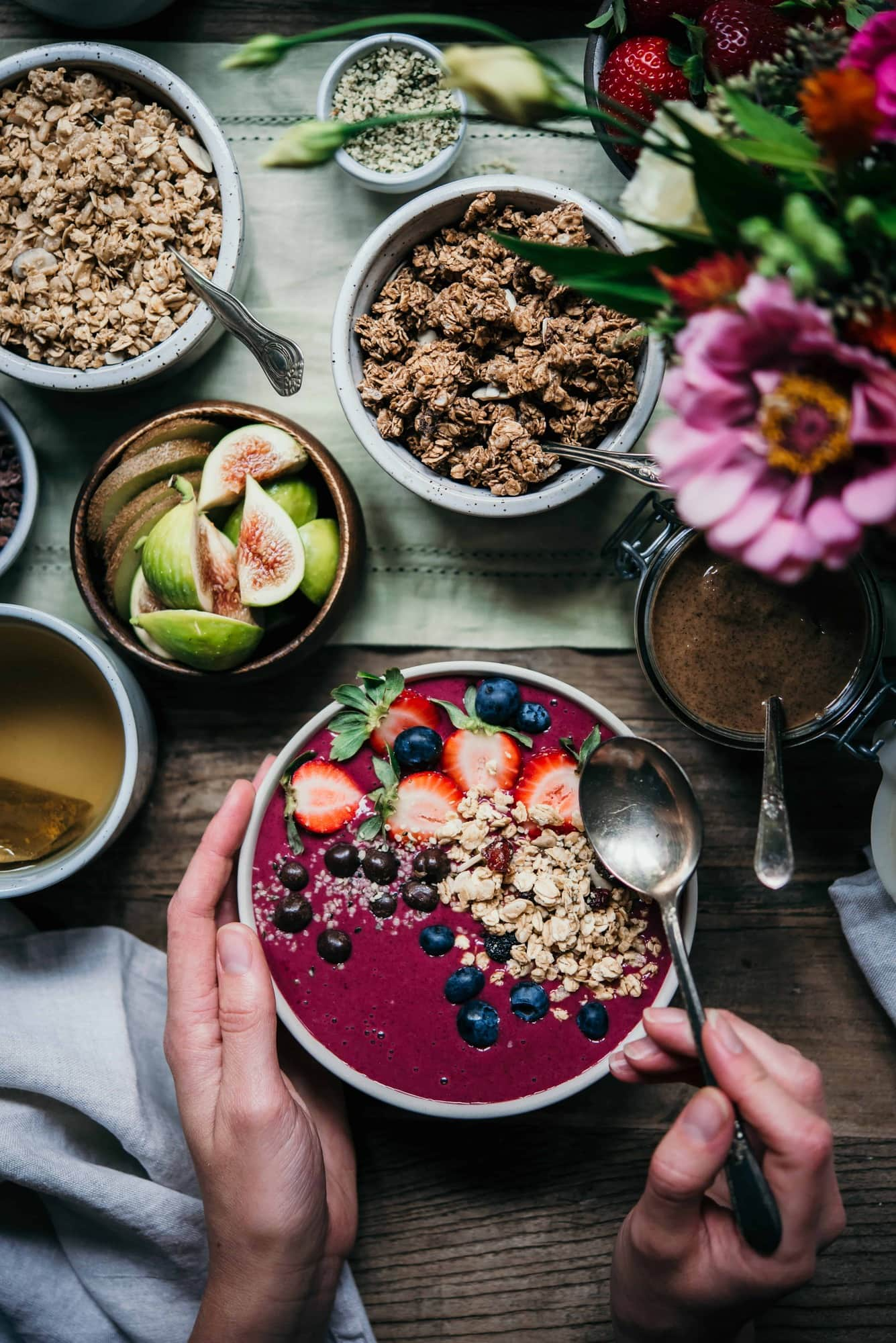 Pink Smoothie Bowl topped with fresh fruit and granola on a table with fresh flowers, bowls of fruit and granola