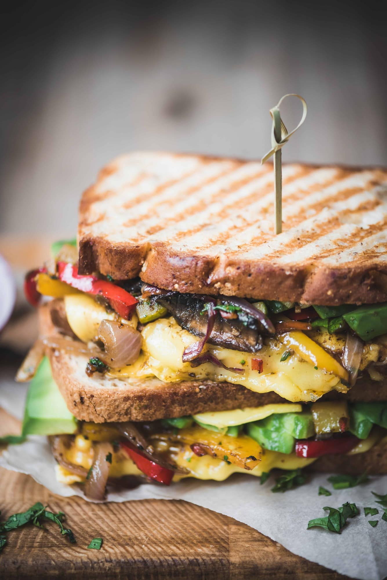 Close up Side view of two stacked fajita paninis with veggies and vegan cheese on a rustic wood cutting board