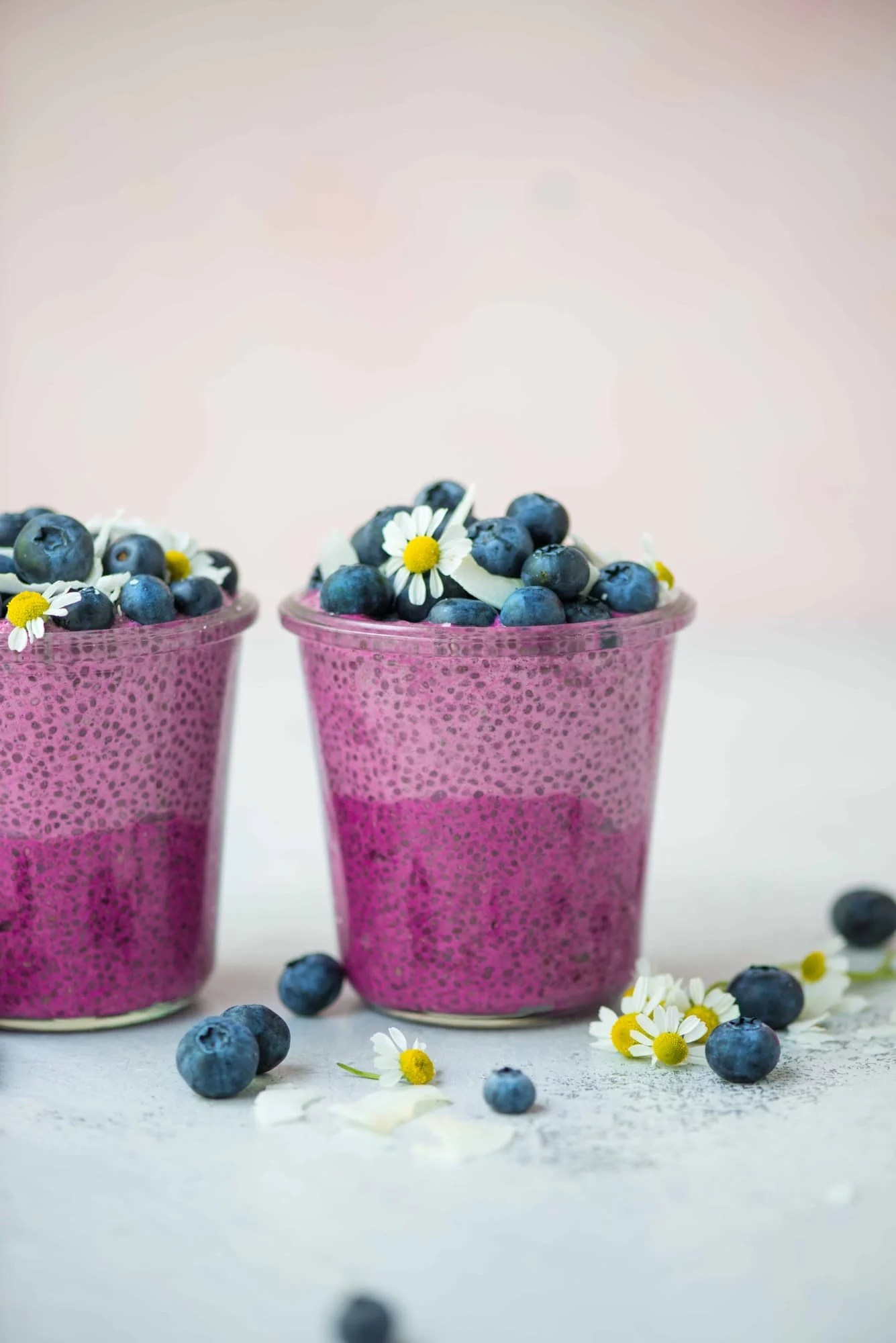 Side view of ombré pink pitaya chia pudding topped with fresh blueberries, coconut and white and yellow flowers