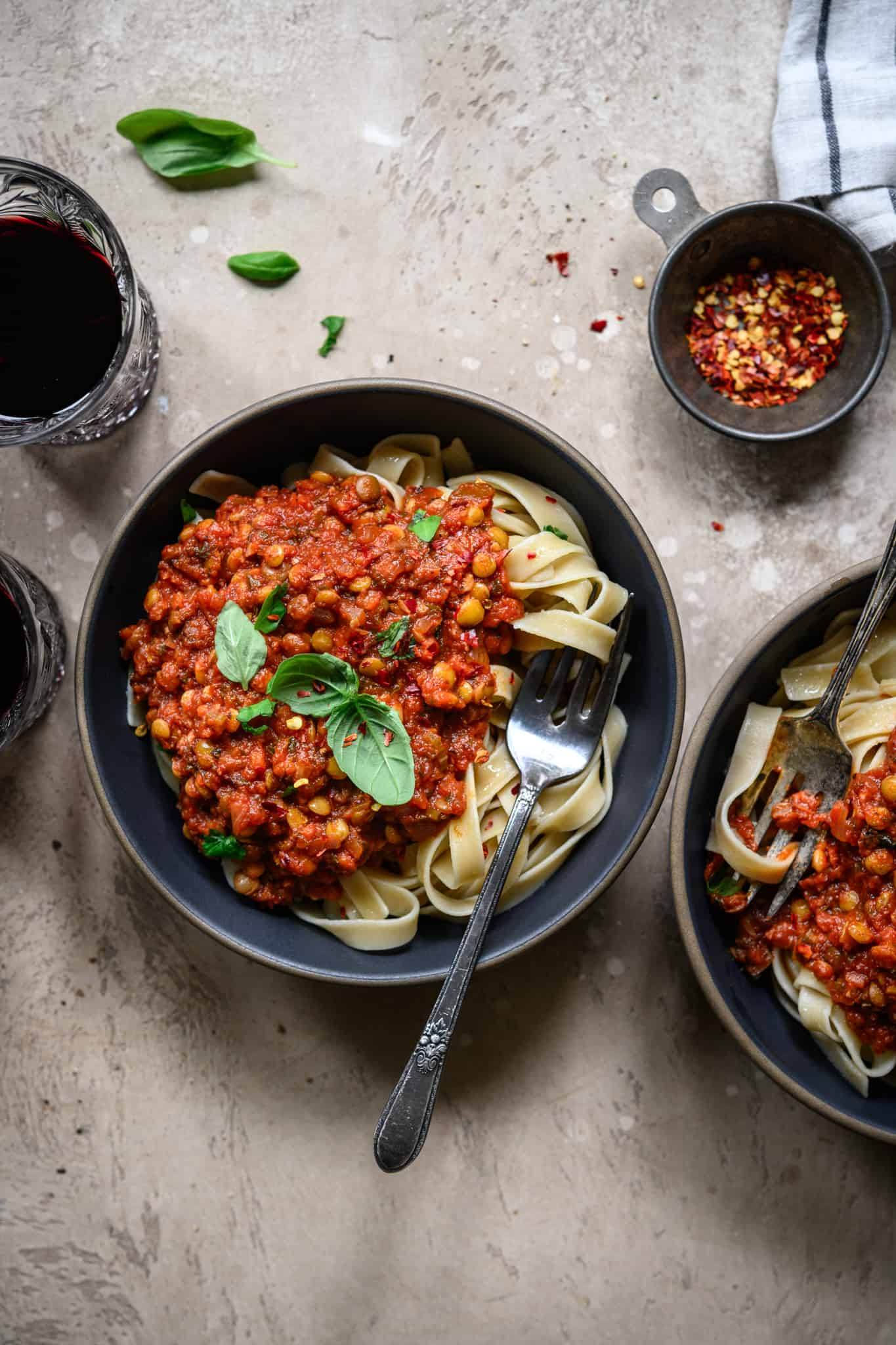 Overhead view of vegan lentil bolognese over pasta in two bowls