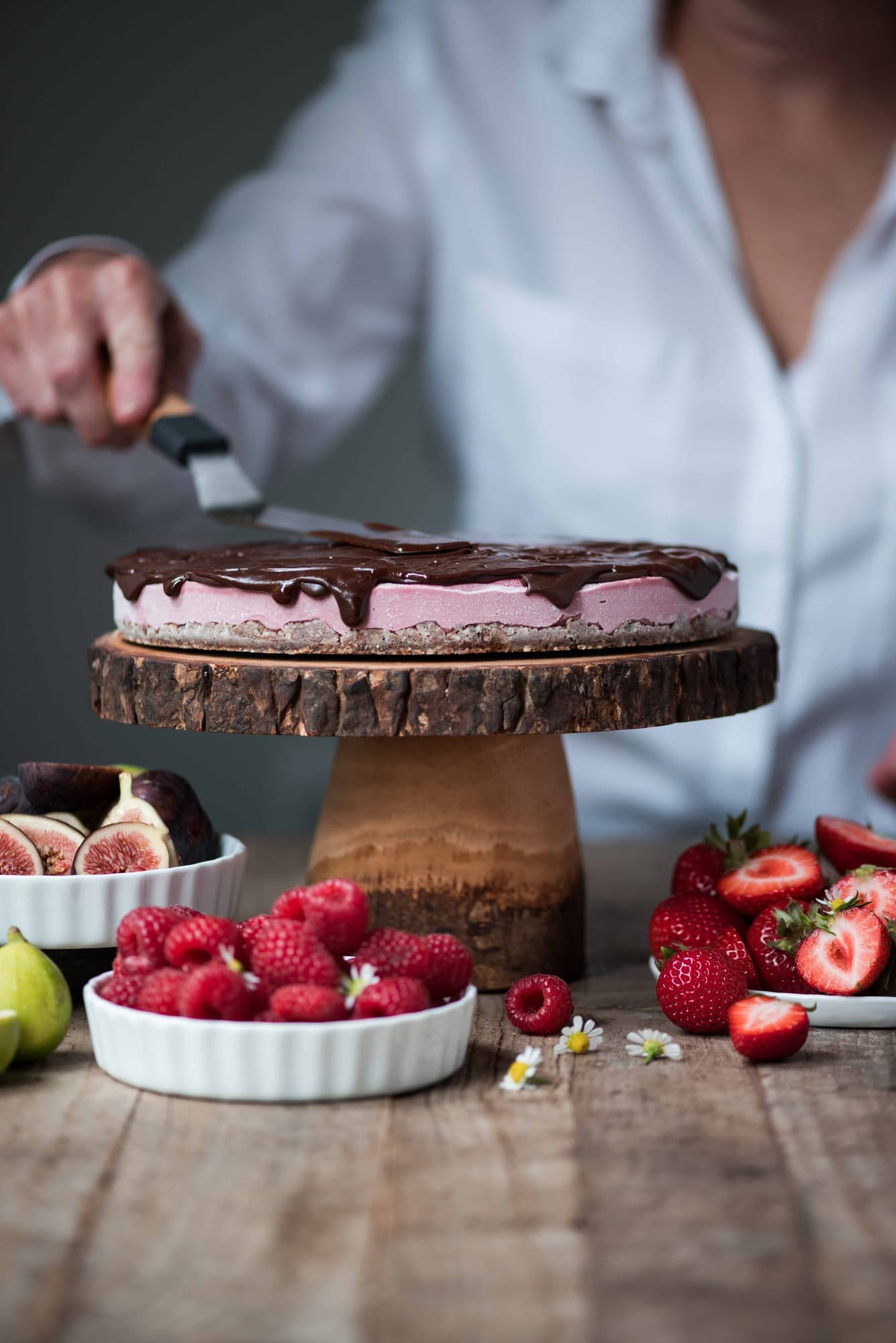 Spreading chocolate ganache on vegan berry cheesecake on wooden cake stand surrounded by bowls of fresh fruit