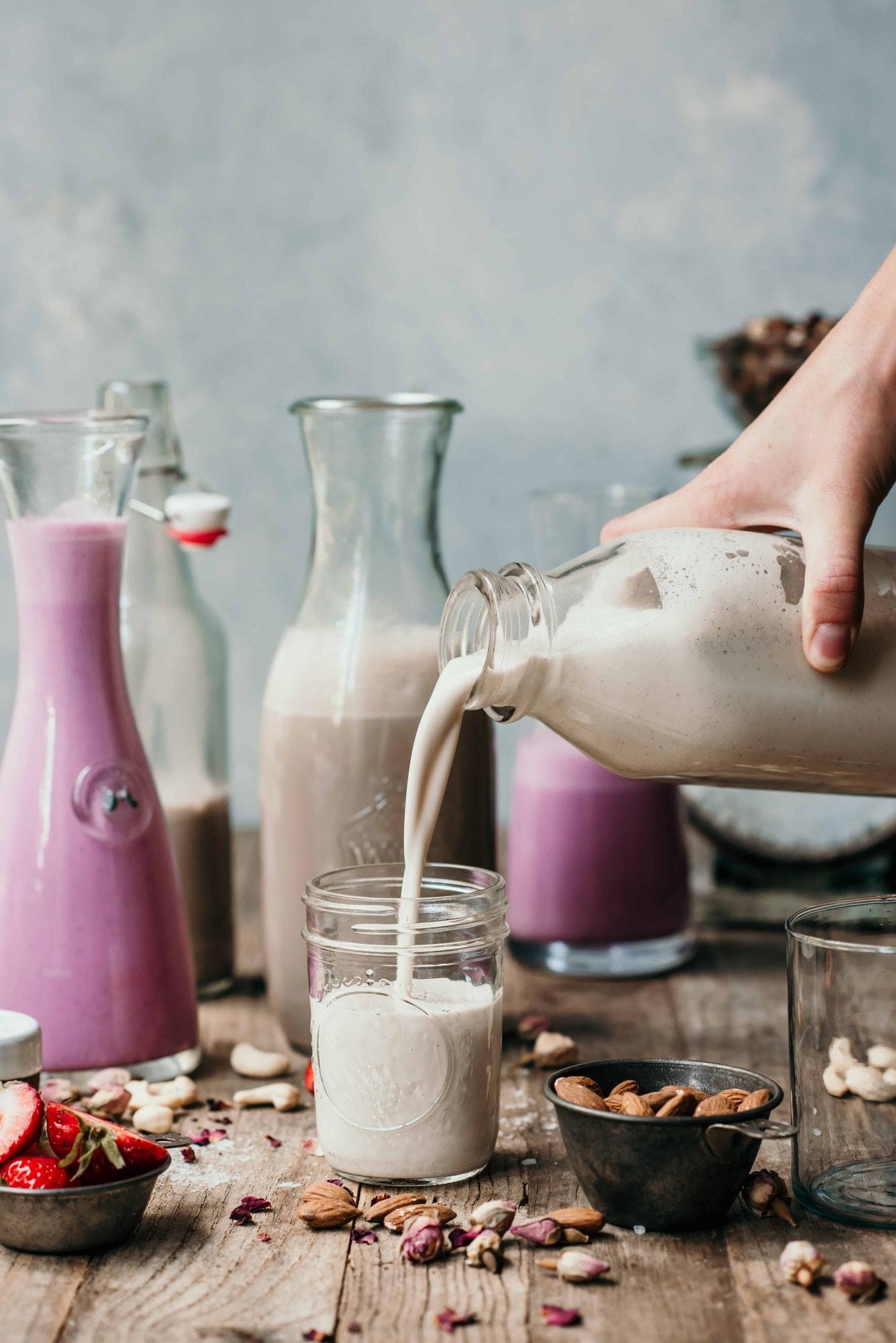 Pouring homemade vanilla almond milk into a glass jar