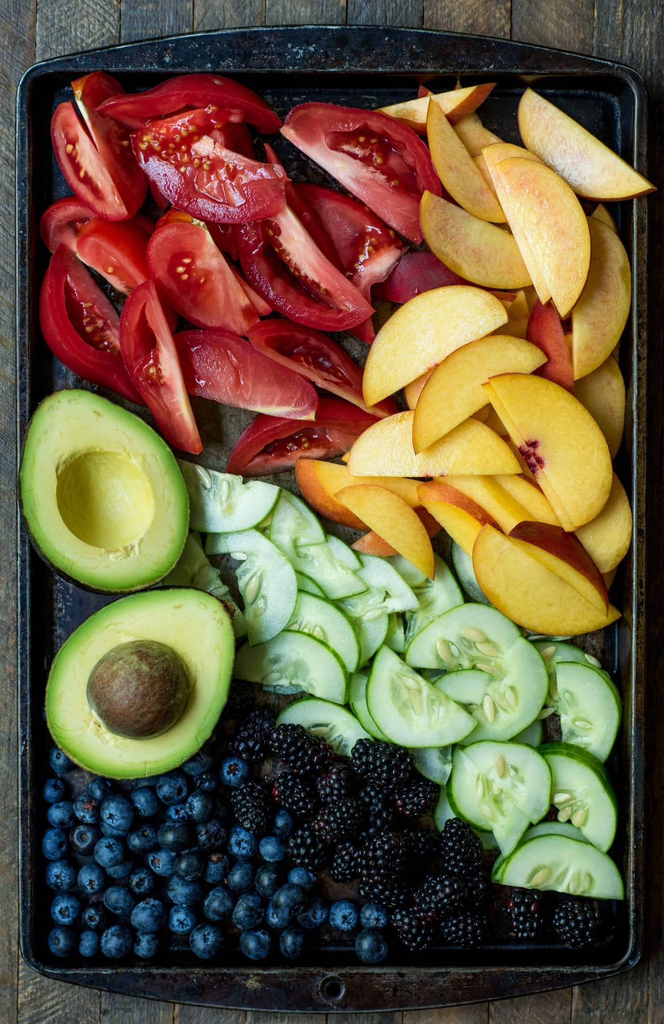 Sheet pan filled with fresh sliced tomatoes, sliced peaches, an avocado, cucumber and blueberries