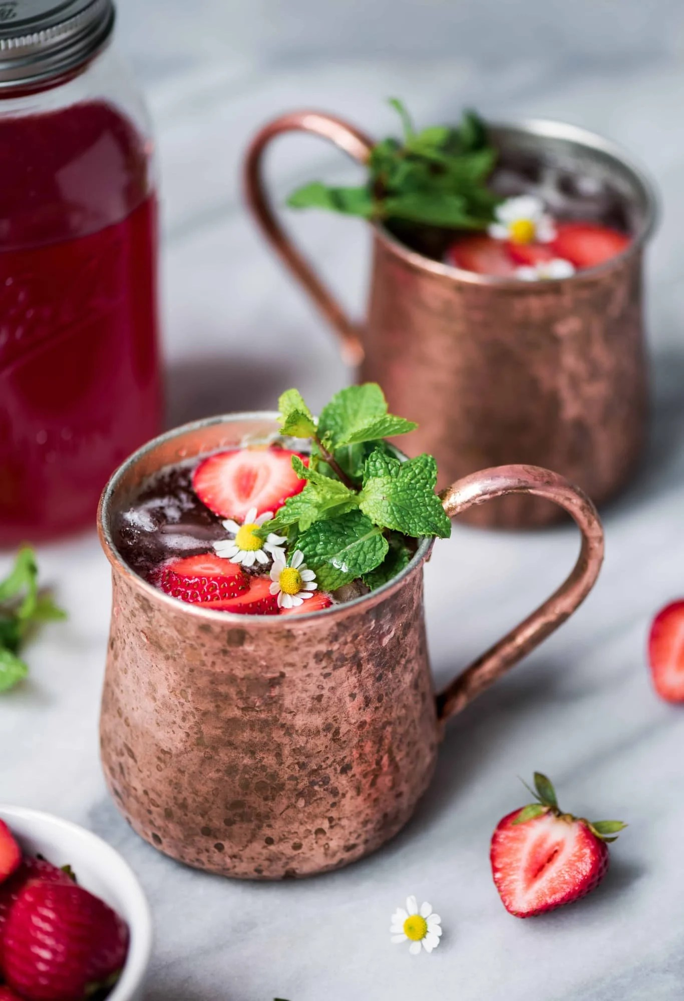 Close up of strawberry moscow mules in copper mugs on marble background