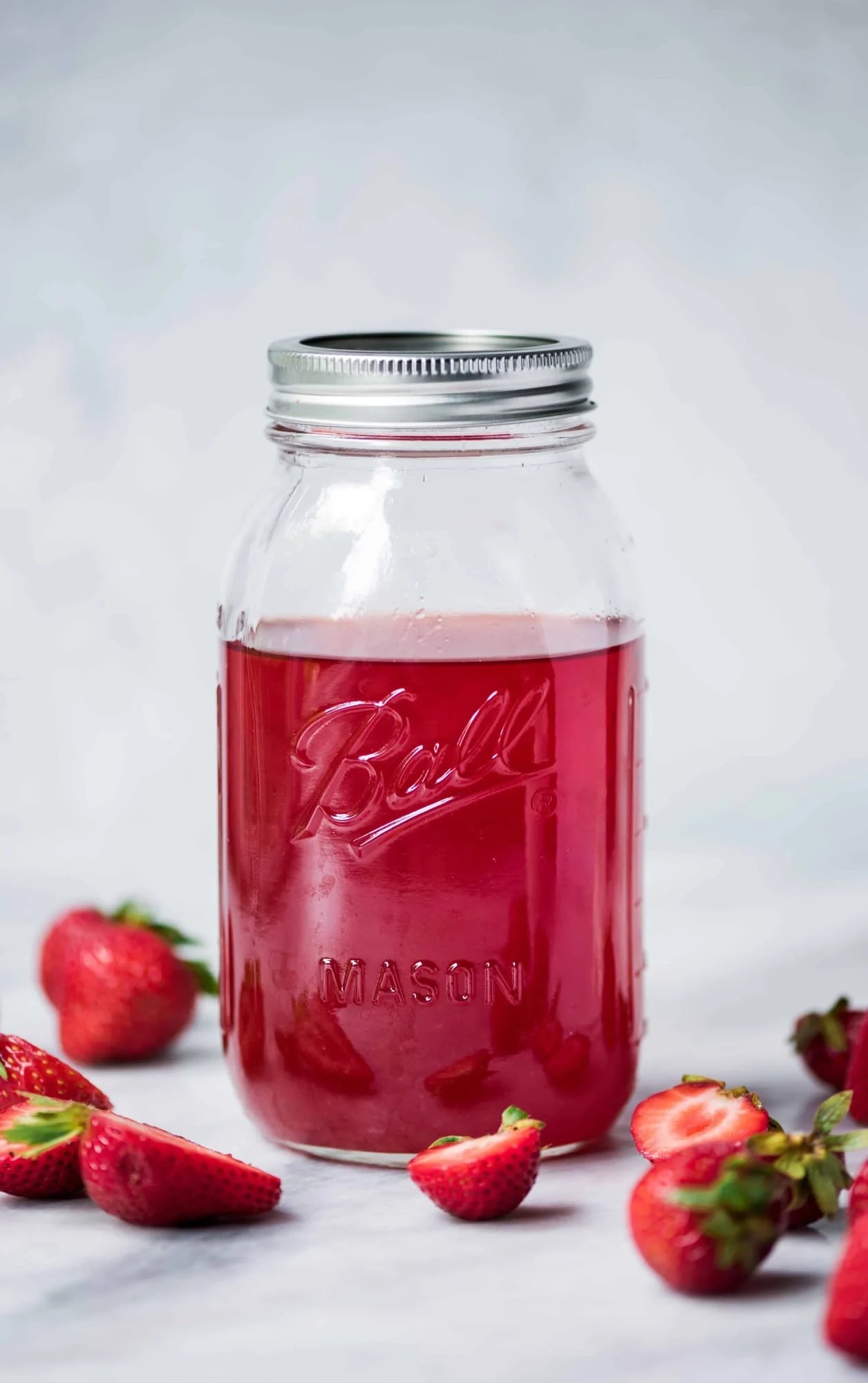 Ball jar of homemade strawberry infused vodka