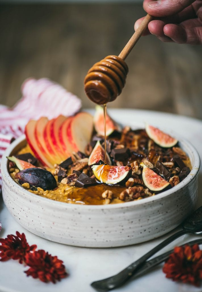 Side view of drizzling maple syrup onto a bowl of pumpkin peanut butter oatmeal topped with caramelized banana, fresh figs, apple, pecans and dark chocolate