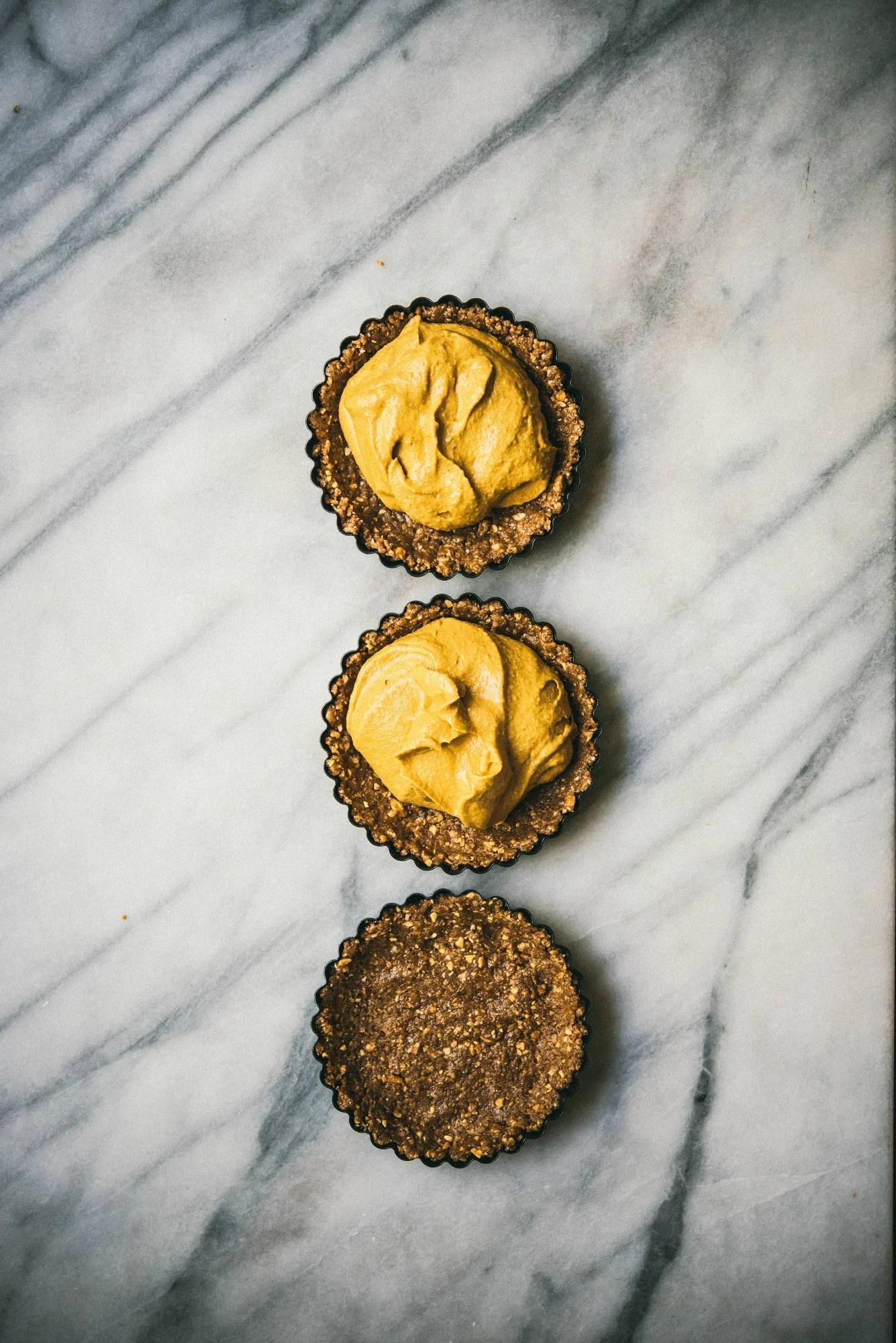 3 mini pumpkin cheesecake tarts on marble surface