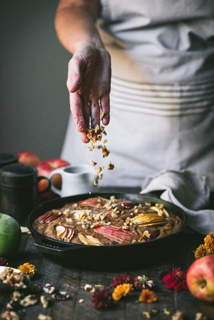 Pouring chopped nuts over an apple cake in a cast iron skillet