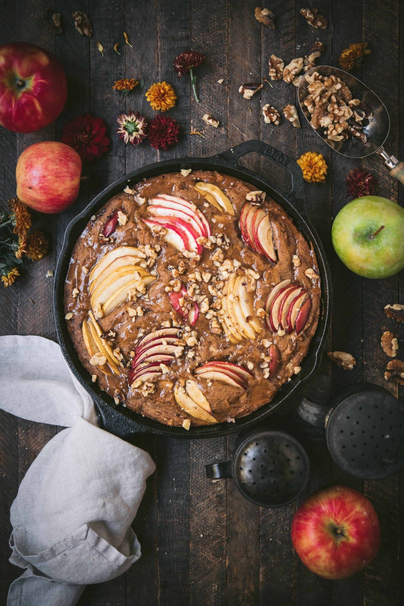 Overhead of an apple walnut cake in a cast iron skillet surrounded by fall flowers and apples