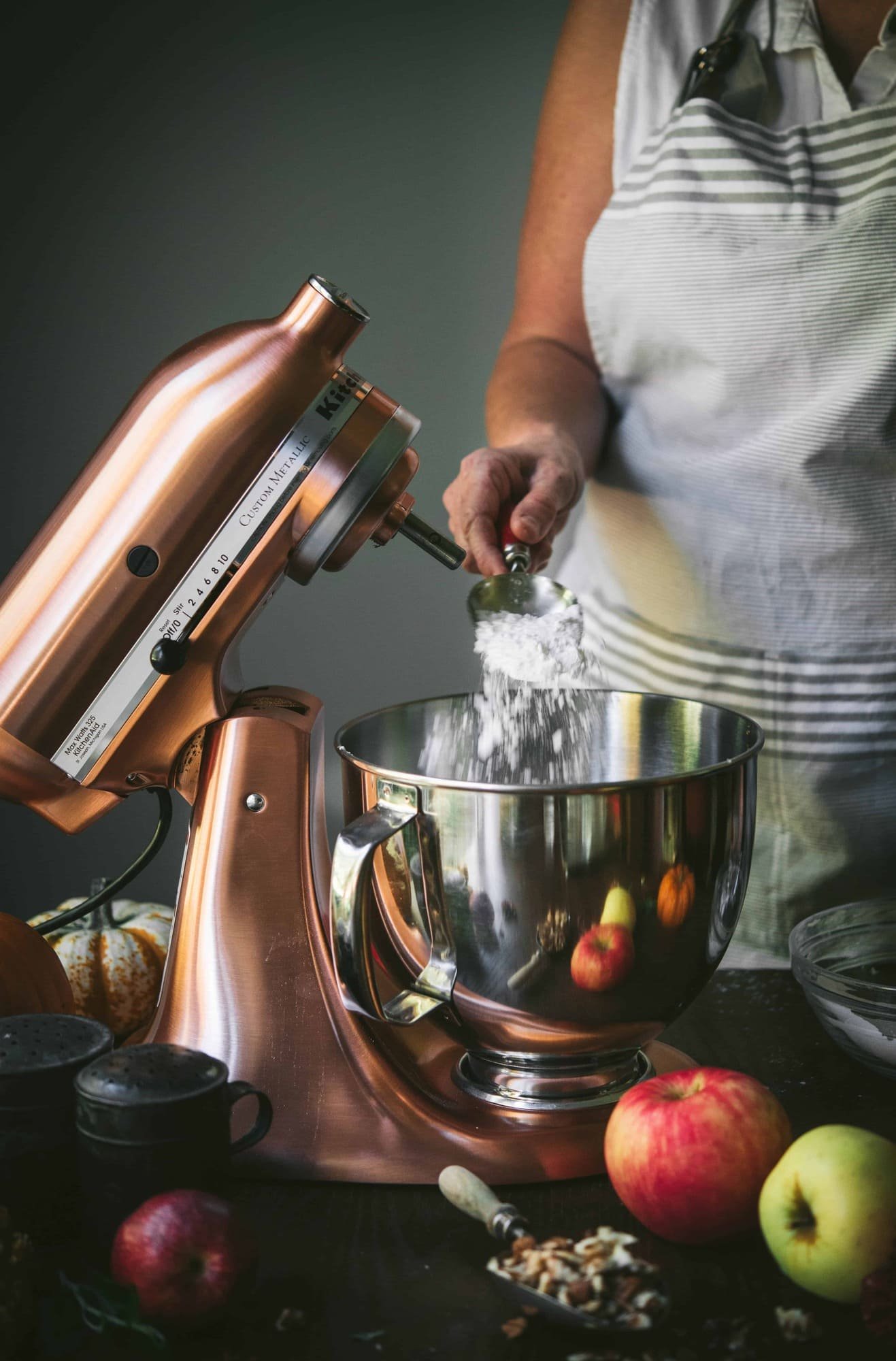 Action shot of pouring flour into a copper stand mixer