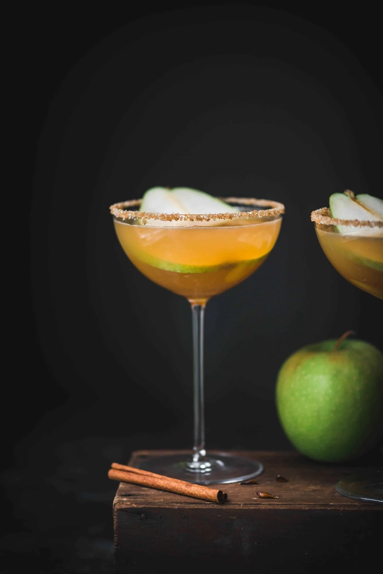 Apple cider pear martini in a long-stemmed coupe glass with dark moody background