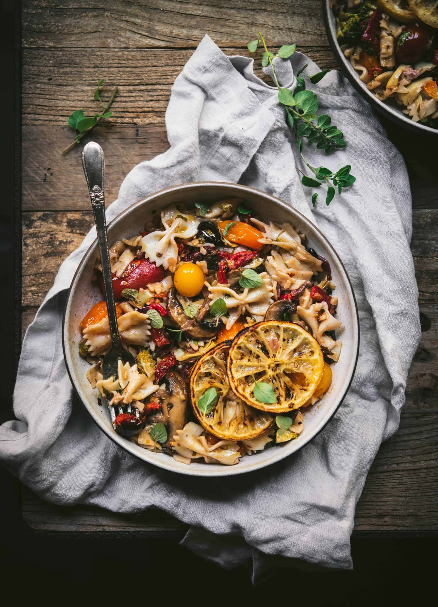 Bowl of bowtie mediterranean pasta with charred lemons on rustic background with fresh herbs